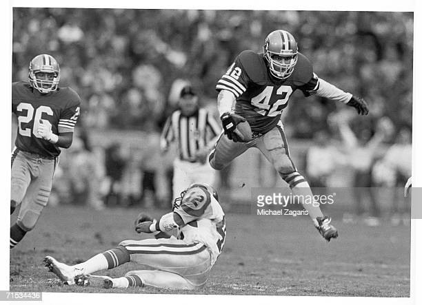 Safety Ronnie Lott of the San Francisco 49ers returns an interception against running back Greg Bell of the Los Angeles Rams as cornerback Darryl...