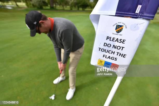 """Safety sign on the flag saying """"Please do not touch the flags"""" as a golfer plays as shot on the green as golf courses reopen in England under..."""