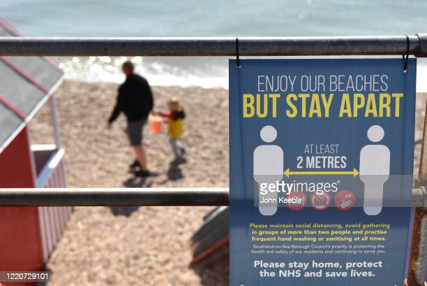 A safety sign warning of social distancing saying Enjoy our beaches but stay at least 2 metres apart as a man and child walk on the beach during...