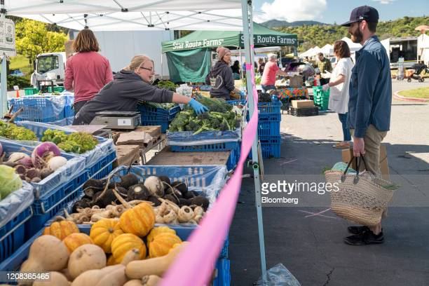 Safety tape keeping shoppers from handling produce is seen at a farmers market in San Rafael, California, U.S., on Thursday, March 26, 2020. Fearful...