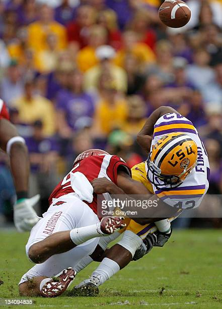 Safety Tramain Thomas of the Arkansas Razorbacks hits running back Michael Ford of the LSU Tigers and causes a fumble that linebacker Alonzo...