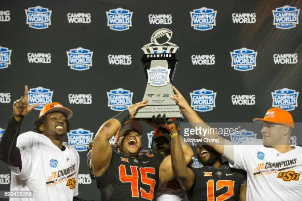 Safety Tre Flowers linebacker Chad Whitener linebacker Kirk Tucker and quarterback Mason Rudolph of the Oklahoma State Cowboys celebrate after...