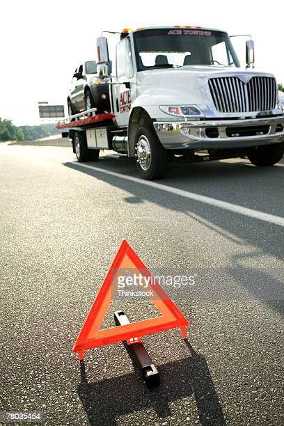 Safety triangle and tow truck on highway