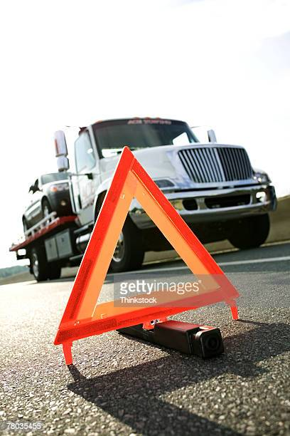 Safety triangle on highway near tow truck