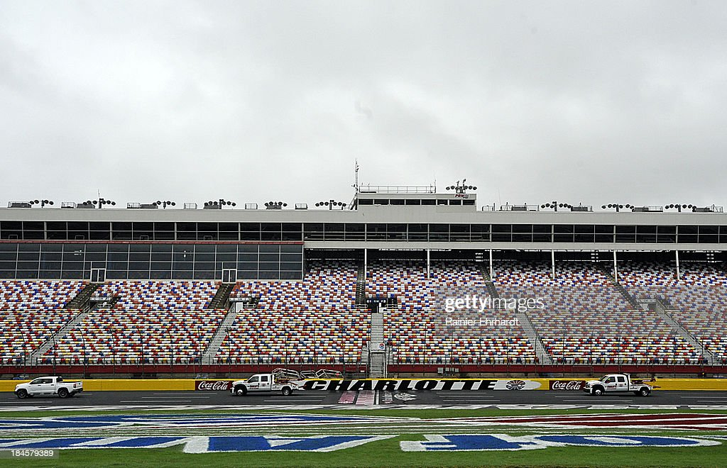 Safety vehicles attempt to dry the track surface before NASCAR Sprint Cup Series testing at Charlotte Motor Speedway on October 14, 2013 in Concord, North Carolina.