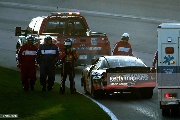 Safety workers assist Martin Truex Jr driver of the Bass Pro Shops/Tracker Boats Chevrolet after he crashed into Denny Hamlin driver of the FedEx...