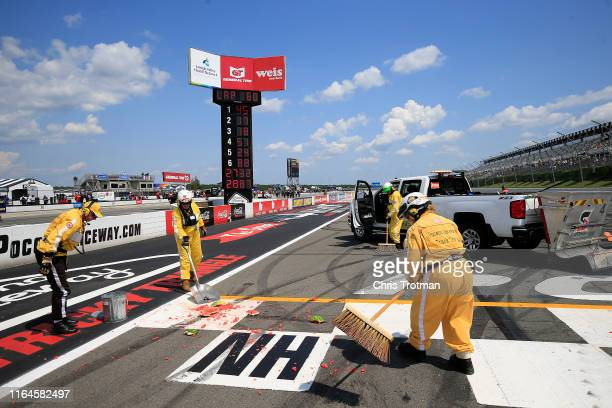 Safety workers clean up a watermelon that was smashed by Ross Chastain driver of the Niece/Acurlite Chevrolet following his victory in the NASCAR...
