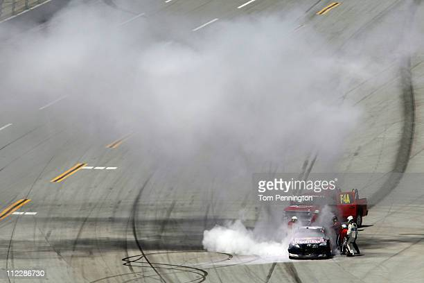Safety workers extinguish the Red Bull Toyota driven by Kasey Kahne after an incident in the NASCAR Sprint Cup Series Aaron's 499 at Talladega...