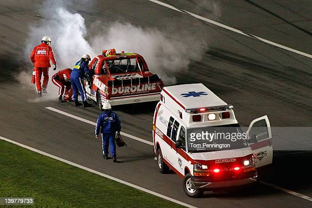 Safety workers tend to Miguel Paludo driver of the Duroline Brakes and Components Chevrolet after hitting the wall during the NASCAR Camping World...