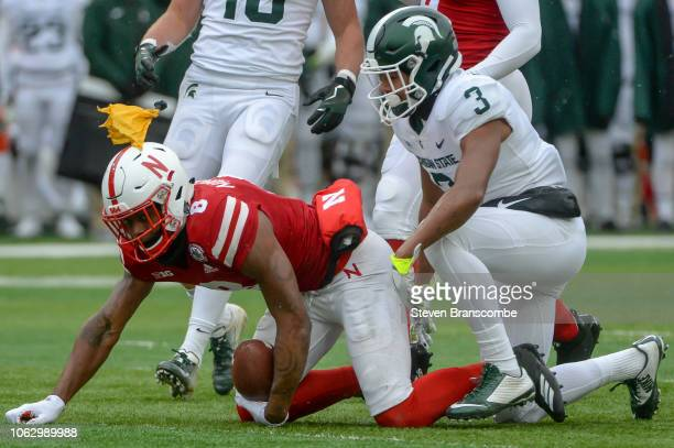Safety Xavier Henderson of the Michigan State Spartans tackles punt returner Stanley Morgan Jr #8 of the Nebraska Cornhuskers after a fair catch call...