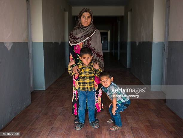 Safia Tajweed, 36 years, stands with her two boys in a hallway at Marastoon, a government-funded institution that houses war widows and women without...