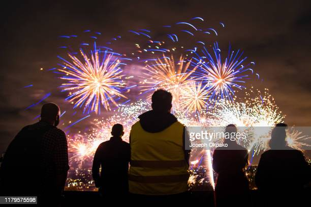 Saftey steward and members of the public watch the firework show during the Alexandra Palace Fireworks 2019 on November 2, 2019 in London, England.
