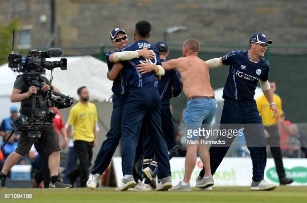 Safyaan Sharif of Scotland is mobbed by his team mates after taking the final wicket of the game as Scotland beat England by 6 runs during the One...