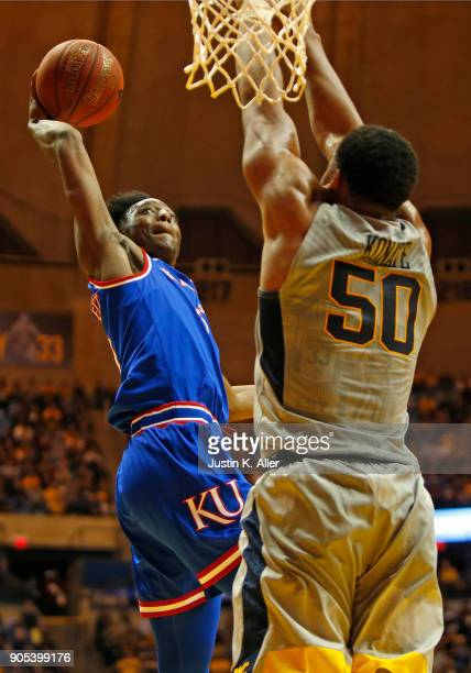 Sagaba Konate of the West Virginia Mountaineers blocks a shot against Devonte' Graham of the Kansas Jayhawks at the WVU Coliseum on January 15 2018...