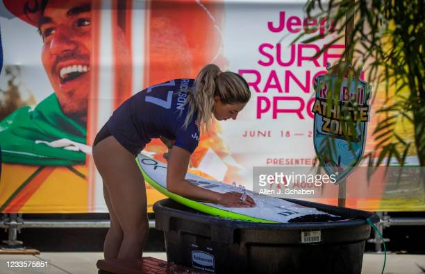Sage Erickson, of Ventura, uses ice to help cool off her melting wax in the triple-digit heat before competing in the womens qualifying rounds...