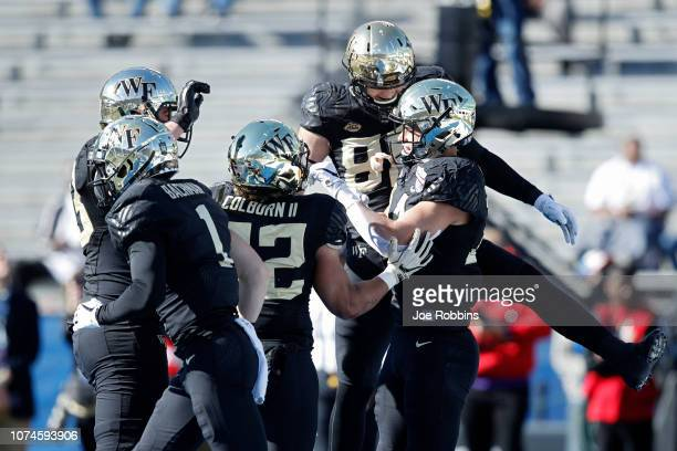 Sage Surratt of the Wake Forest Demon Deacons celebrates with teammates after making a nineyard touchdown reception against the Memphis Tigers in the...