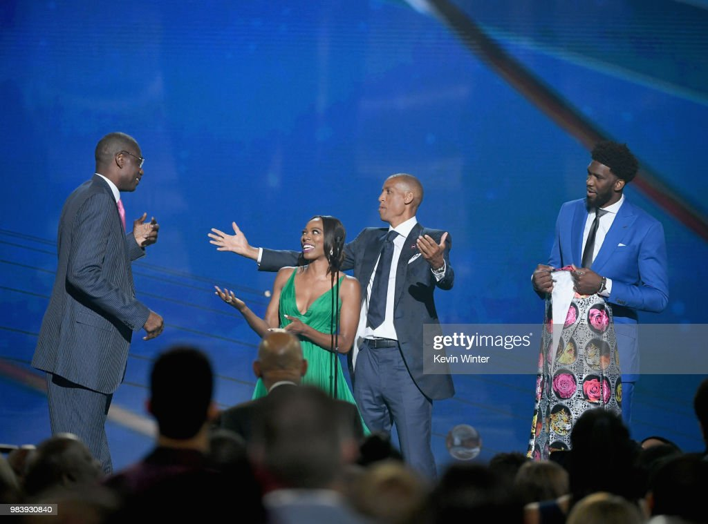 Sager Strong award winner Dikembe Mutombo accepts his jacket from Yvonne Orji, Reggie Miller, and Joel Embiid onstage at the 2018 NBA Awards at Barkar Hangar on June 25, 2018 in Santa Monica, California.