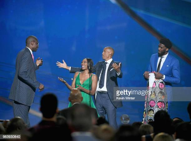 Sager Strong award winner Dikembe Mutombo accepts his jacket from Yvonne Orji Reggie Miller and Joel Embiid onstage at the 2018 NBA Awards at Barkar...