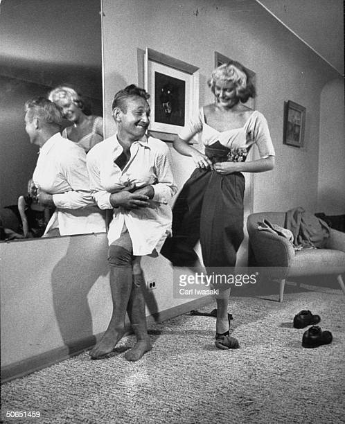 Sagging Robert Curtis bending over to save bosom while Germaine Delbecque has trouble zipping up the pants