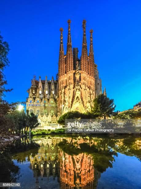 Sagrada Familia illuminated at dusk with reflection on lake in Barcelona, Catalonia, Spain