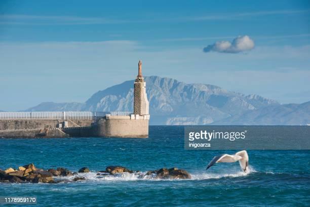 sagrado corazon de jesus statue in harbour, tarifa, cadiz, andalusia, spain - cádiz fotografías e imágenes de stock