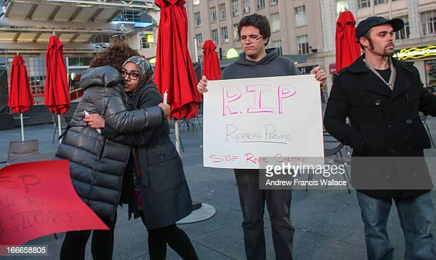 Sahar Zairab hugs Nova Browning Rutherford during a vigil at Yonge and Dundas square to mark the passing of bullying victim Rehtaeh Parsons