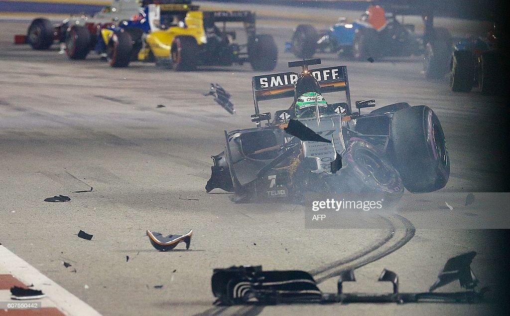 TOPSHOT - Sahara Force India F1 Team's German driver Nico Hulkenberg crashes during the Singapore Grand Prix night race on September 18, 2016. / AFP / POOL / Jeremy LEE