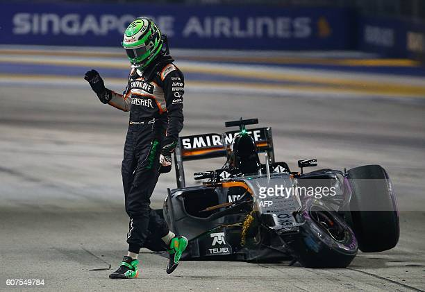 Sahara Force India F1 Team's German driver Nico Hulkenberg leaves his car after crashing during the start of the Formula One Singapore Grand Prix in...