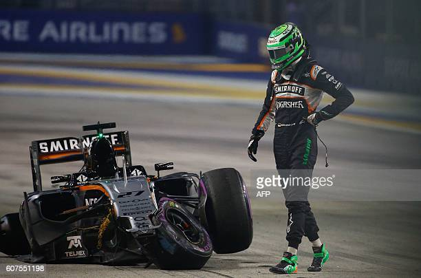 Sahara Force India F1 Team's German driver Nico Hulkenberg looks at his car after crashing during the start of the Formula One Singapore Grand Prix...