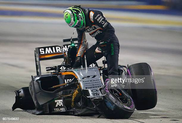 Sahara Force India F1 Team's German driver Nico Hulkenberg steps out of his car after crashing during the Singapore Grand Prix night race on...