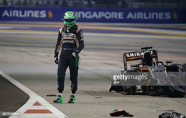 Sahara Force India F1 Team's German driver Nico Hulkenberg walks away from his car after crashing during the start of the Formula One Singapore Grand...