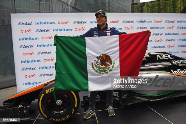 Sahara India Force Mexican driver Sergio 'Checo' Perez poses for pictures holding his national flag after a press conference in Mexico City on...