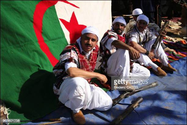 Saharan dancers from Ghardaia in their traditional garb with their wooden carbines and the Algerian flag in the background