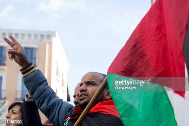 Saharawi man makes a victory symbol during the demonstration. Thousands of Saharawis arrive from all over Spain to demand the end of Morocco's...