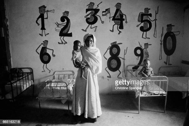 A Saharawi woman holds one of her young students in a Polisario kindergarten or preschool in Western Sahara The Polisario Front was formed in 1973 as...