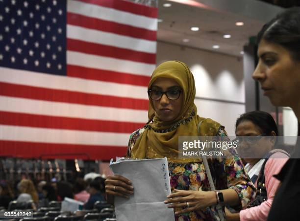 Saher Jangdah picks up her certificate after pledging allegiance to the United States of America to become a US citizen during a naturalization...