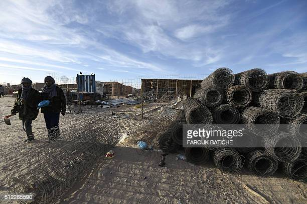 Sahrawi men walk past metal wires in the Smara refugee camp in Algeria's Tindouf province on February 25 2016 / AFP / Farouk Batiche