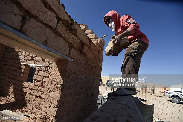 A Sahrawi refugee man rebuilds a house which was destroyed during heavy rain last year at the Samara refugee camp west of the Algerian city of...