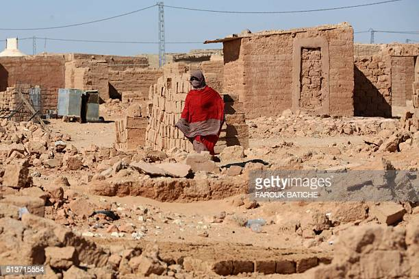 A Sahrawi refugee woman walks amid the rubble of which were destroyed during heavy rain last year at the Samara refugee camp west of the Algerian...