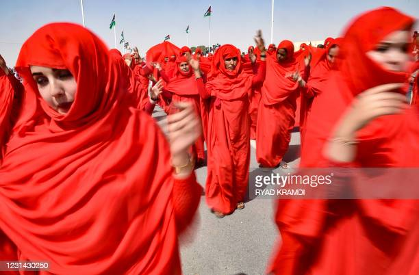 Sahrawi women perform a dance following a military parade during celebrations marking the 45th anniversary of the declaration of the Sahrawi Arab...