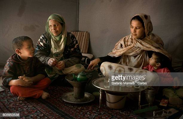 Sahrawi women with their children prepare the tea inside the tent in the Saharawi refugee camp Smara on January 16 2008 in Tindouf Algeria