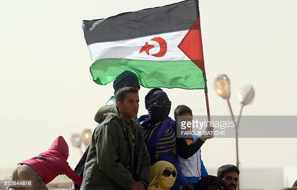 Sahrawis hold a Polisario Front's flag during a ceremony to mark 40 years after the Front proclaimed the Sahrawi Arab Democratic Republic in the...