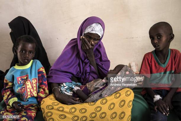 Sahro Mohamed Mumin looks at her son Abdulrahman Mahamud who was diagnosed with pneumonia and severe malnutrition at a government run health clinic...