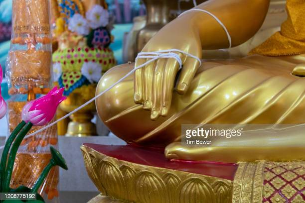 sai sin sacred thread tied to buddhas for boon khun lan during boon khao jee at wat chan. - tim bewer fotografías e imágenes de stock