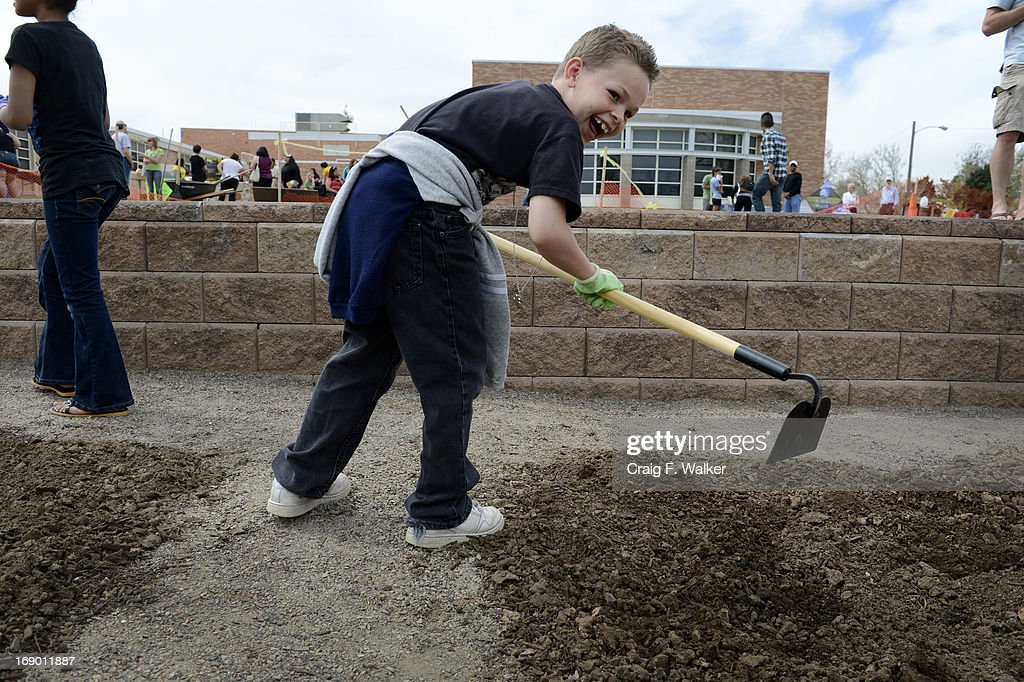 Saiah Brydon, 8, enjoys working during the North Middle School Garden Festival in Aurora, CO May 18, 2013. The youths had just been informed that the worm castings they were smelling is also called 'worm poop.' The celebration marked the opening of the first school-based community garden in Aurora Public Schools. The project, funded by The Piton Foundation, was made possible through a partnership of Aurora Public Schools, Denver Urban Gardens (DUG), and Anschutz Medical Campus Department of Family Medicine and BRANCH, a multi-disciplinary student organization from the medical campus. A second garden is scheduled to open later this year at Hinkley High School.