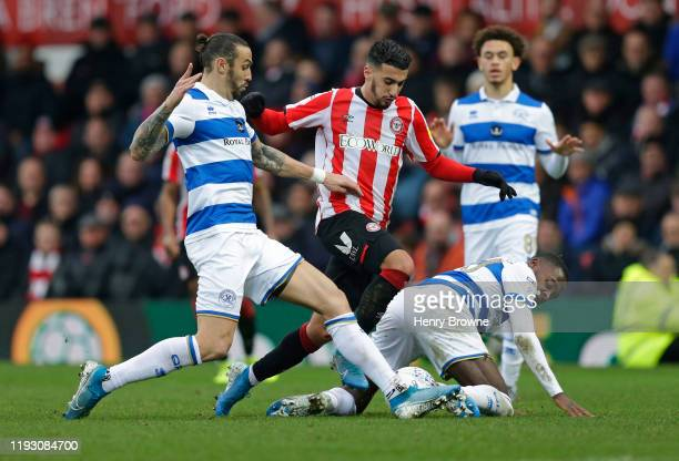 Said Benrahma of Brentford tackled by Bright OsayiSamuel and Geoff Cameron of Queens Park Rangers during the Sky Bet Championship match between...