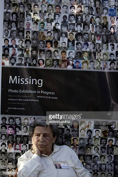 Saide the sister of missing person Butros Khawand sits under an poster advertising a photo exhibition called Missing during a demonstration by...