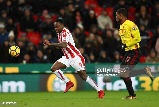 Saido Berahino of Stoke City runs with the ball under pressure from Jerome Sinclair of Watford during the Premier League match between Stoke City and...