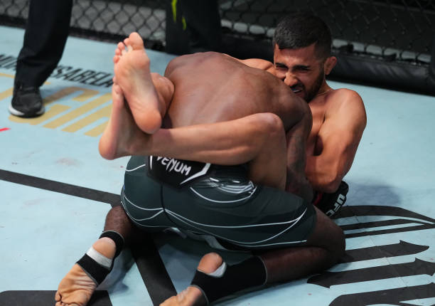 Saidyokub Kakhramonov of Uzbekistan attempts to secure a guillotine choke submission against Trevin Jones of Guam in a bantamweight fight during the...