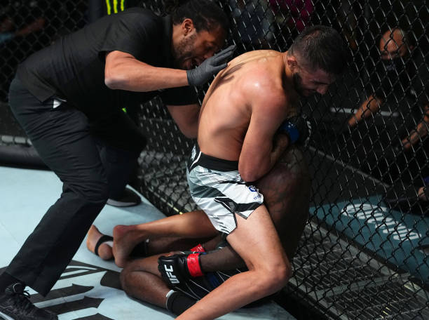 Saidyokub Kakhramonov of Uzbekistan secures a guillotine choke submission against Trevin Jones of Guam in a bantamweight fight during the UFC Fight...